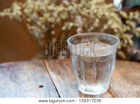 Glass water with dry flower on wooden table.Focus on glass.