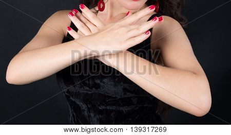 The girl's hands symmetrically crossed on the chest with red nails. On a dark background.