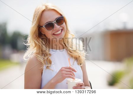 Smiling stylish blonde drinking milkshake or smoothies outdoors in summer sunny day