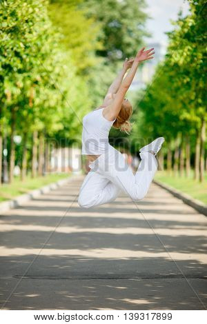 Young woman jumping high in city park. Symbol of freedom