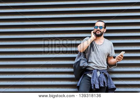 people, technology, travel and tourism - man with earphones, smartphone and bag on city street and listening to music