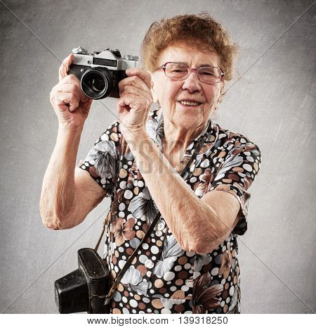 Granny photographer. Old woman with camera. Senior studio shot
