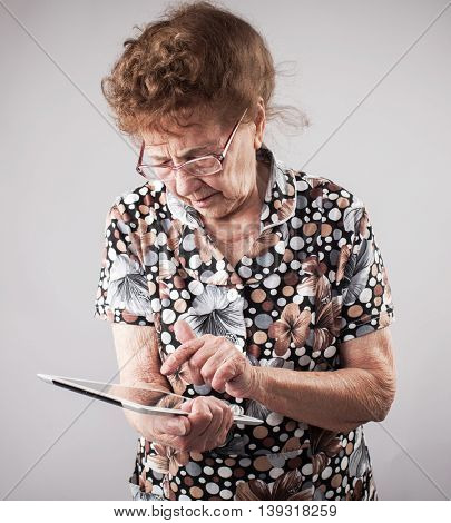 Old woman holding a tablet in the hands of. Seniors with tablen pc