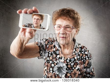 Old woman photographed yourself on the mobile phone. Fan granny makes selfie
