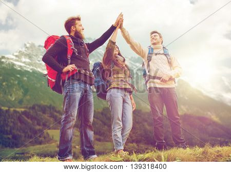 travel, tourism, hike, gesture and people concept - group of smiling friends with backpacks making high five over alpine mountains and hills background