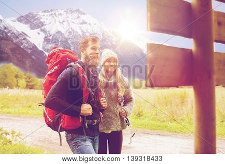 adventure, travel, tourism, hike and people concept - smiling couple with backpacks standing at signpost over alpine mountains and hills background