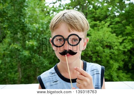 Cute young boy holding a disguise of glasses and moustache to his face.