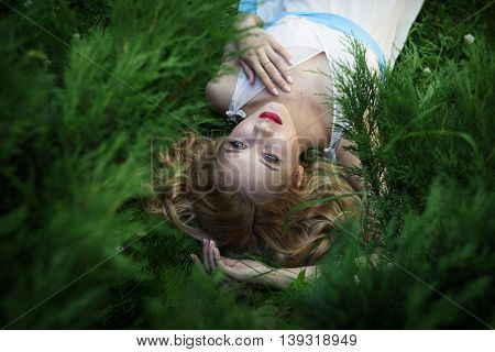 Beautiful girl lying and resting on a grass in a summer park