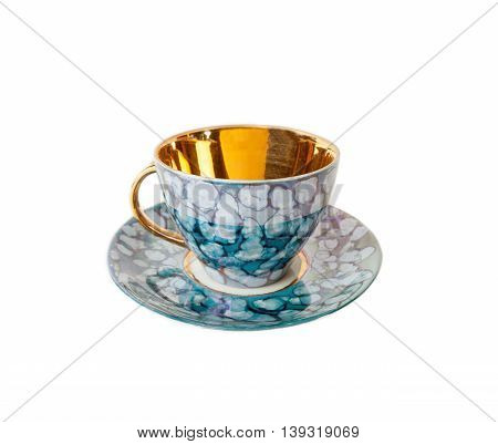 Vintage teacup and saucer in blue and gold isolated over white