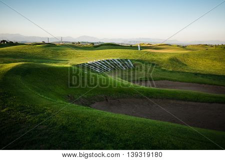 Beautiful golf course with sand trap and mountains in the background at sunset
