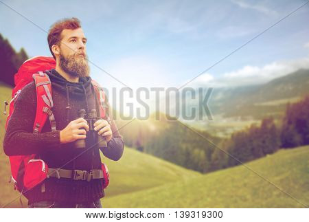 adventure, travel, tourism, hike and people concept - man with red backpack and binocular over alpine mountains and hills background