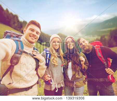 adventure, travel, tourism, hike and people concept - group of smiling friends with backpacks making selfie over alpine mountains and hills background