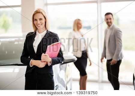 Elegant young salesperson working at car dealership