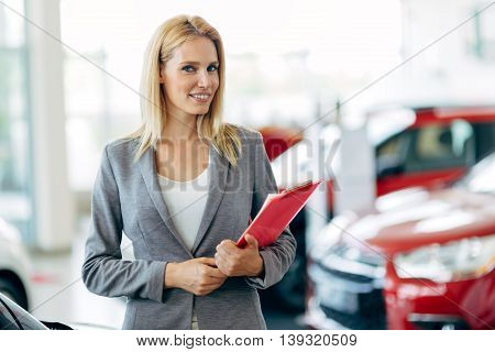 Professional young salesperson working in car dealership