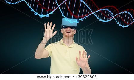 3d technology, virtual reality, cyberspace, entertainment and people concept - happy young man with virtual reality headset or 3d glasses playing game and looking at dna molecule over black background