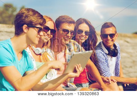 friendship, leisure, summer and people concept - group of smiling friends with tablet pc computer sitting outdoors