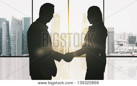 business, teamwork, partnership, cooperation and people concept - partners shaking hands over office window and singapore city skyscrapers background and sun light