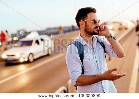 Handsome man waiting for and calling taxi