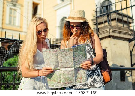 Two attractive woman tourists looking at the map in city. Vacation concept.Summer vacation.