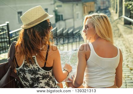 Rear view of two young women with city map in search of attractions. Young tourist girls friends traveling on a holidays. Summer vacation.