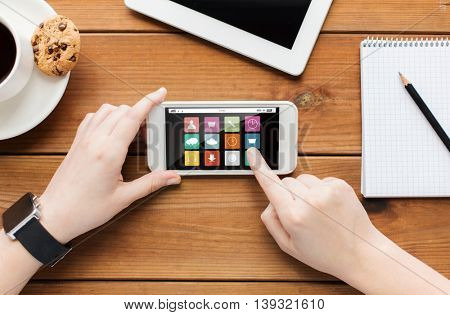 technology, business, media and people concept - close up of woman hands with menu icons on smartphone screen and coffee cup on wooden table