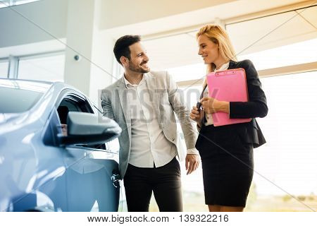 Customer looking at cars at dealership and talking to salesperson