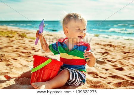 one year old boy smiling at the beach. Child on vacations at sea