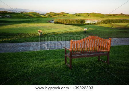 Walkway with bench near golf course over the lake with trees on background at sunset