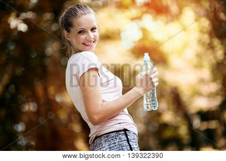 Dehydrated young beautiful female jogger drinking water