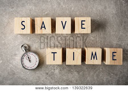 Stopwatch and wooden cubes with space for text on grey background