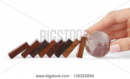 Transparent glass earth ball blocked falling dominoes row, isolated on white