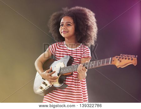 Afro-American little girl with curly hair playing guitar on colour background