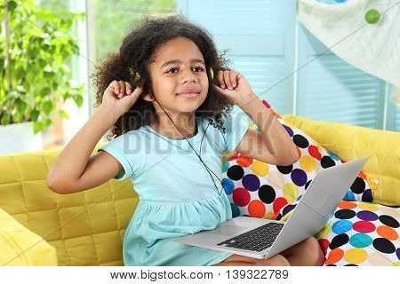 Afro-American little girl with headphones and laptop on sofa in room