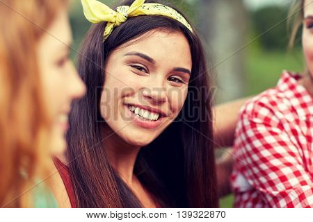 friendship, leisure, summer and people concept - happy young woman with group of friends outdoors