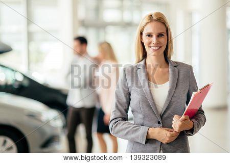 Elegant eautiful salesperson working at car dealership