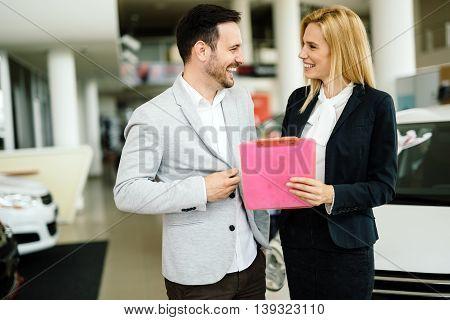 Elegant beautiful salesperson working at car dealership