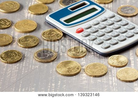 Euro coins and digital calculator on wooden background