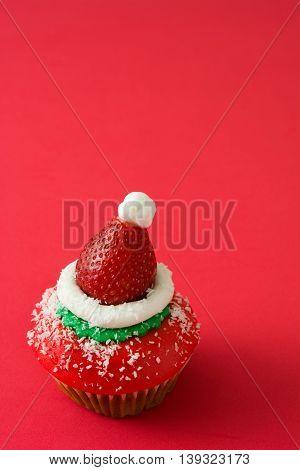 Sweet santa hat cupcake on red background