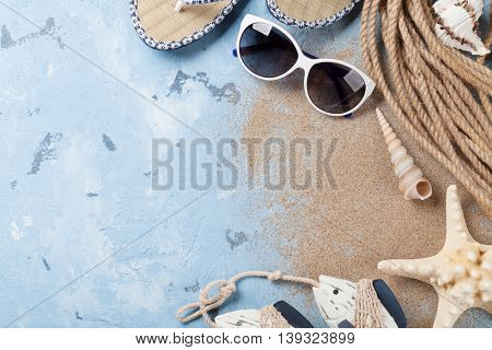 Beach accessories. Sunglasses, flip-flops and sea shells on stone background. Top view with copy space