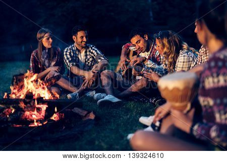 Friends enjoying music near campfire at night