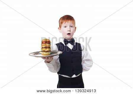 Little waiter stands with tray serving big double hamburger. Smiling redhead child boy in suit plays restaurant servant, gives burger isolated at white background