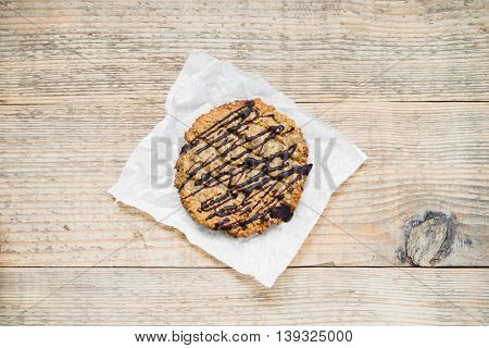 Oatmeal cookie with chocolate topping arranged on baking paper and old rustic table. top view.