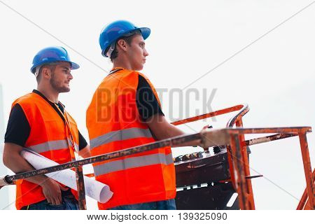 Construction workers operating on machine, side view