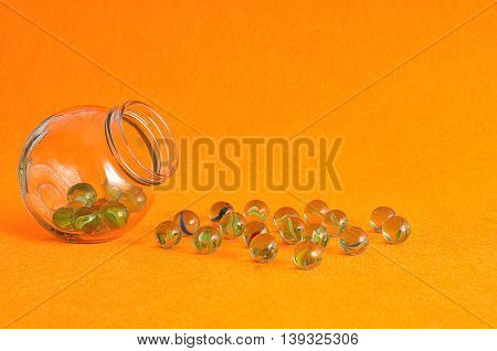 A collection of marbles in a glass jar displayed on an orange background