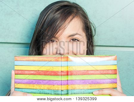 Beautiful Lady Smiling Behind Colorful Notebook Or Agenda
