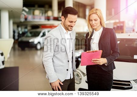 Customer looking for a car at dealership and customizing vehicle