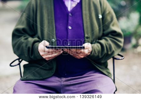 closeup of an old caucasian man using a tablet computer outdoors