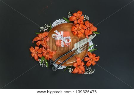 Terracotta plate decorated with orange lilies flowers and gift box tied with white lace ribbon and exclusive forged cutlery on a black table; top view flat lay