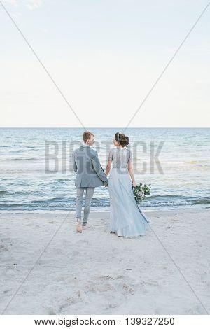 Newly-weds making a walk along the beach.