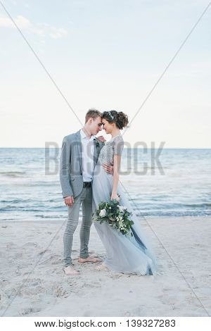 Groom holding in arms bride by the sea.